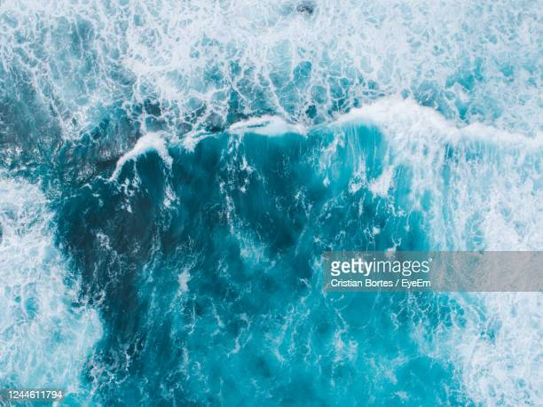 aerial view of waves of blue sea water - bortes stockfoto's en -beelden