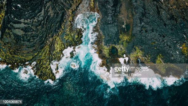 aerial view of waves rushing at beach - rock formation stock pictures, royalty-free photos & images