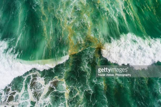 aerial view of waves splashing in sea. - rough stock pictures, royalty-free photos & images