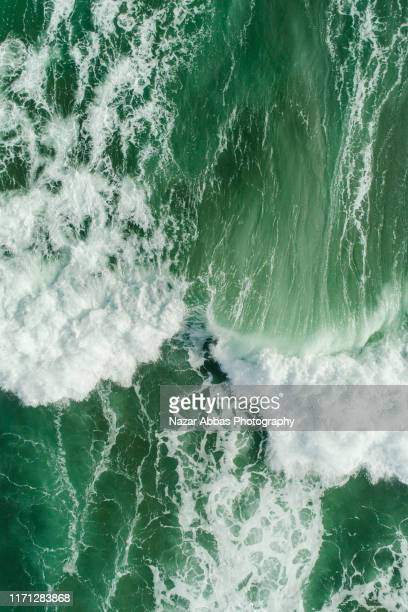 aerial view of waves splashing in sea. - nazar abbas photography stock pictures, royalty-free photos & images