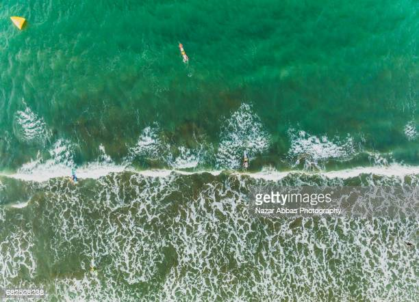 Aerial View Of Waves Splashing On Beach and People Surfing, Auckland, New Zealand.