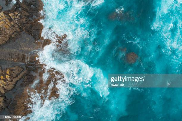 aerial view of waves splashing on beach. - tide stock pictures, royalty-free photos & images