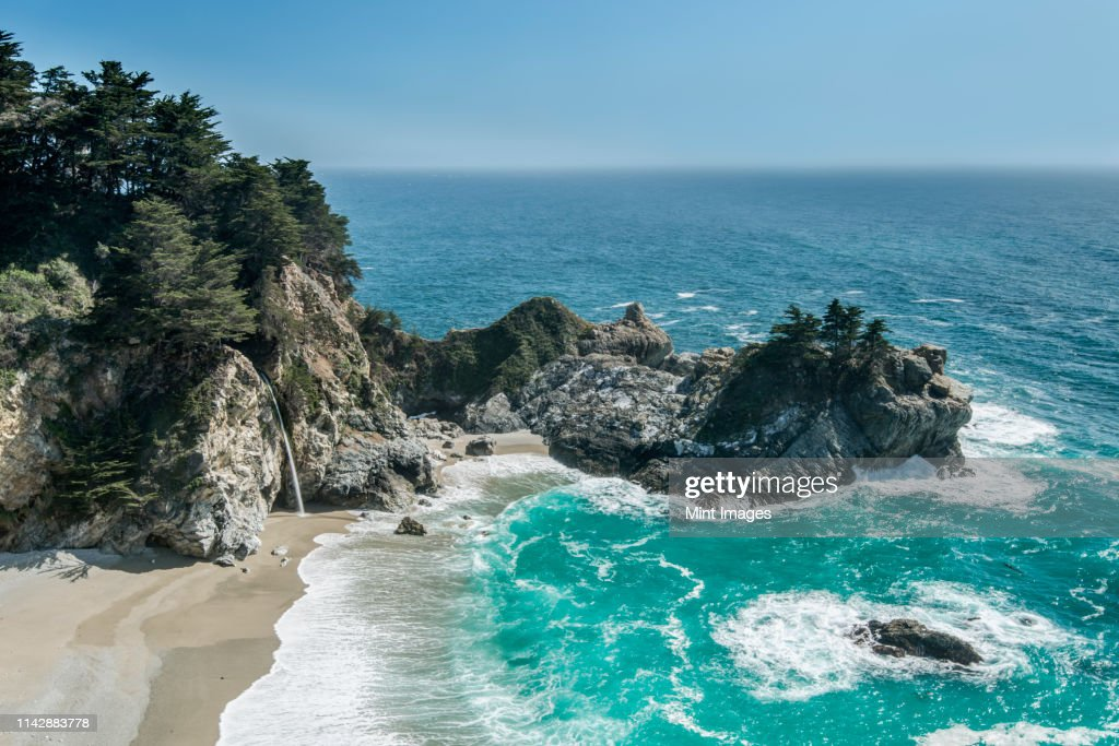 Aerial view of waves washing up on rocky beach : Stock Photo