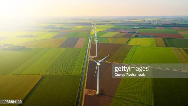 aerial view of wind turbines in a row and bright sun - netherlands stock pictures, royalty-free photos & images