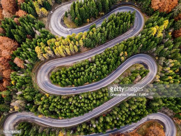 aerial view of winding road amidst tree - rumania fotografías e imágenes de stock