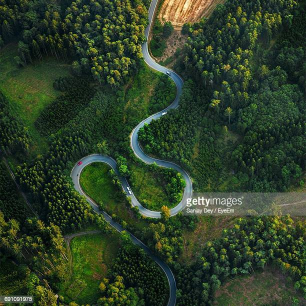 aerial view of winding road amidst trees - road stock pictures, royalty-free photos & images