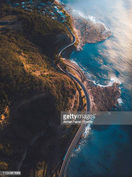 aerial view of winding road by sea - vertical stock pictures, royalty-free photos & images