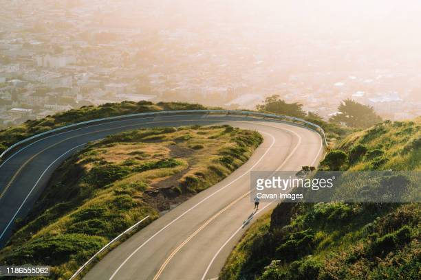 aerial view of winding road on mountain against cityscape during sunset - california stock pictures, royalty-free photos & images
