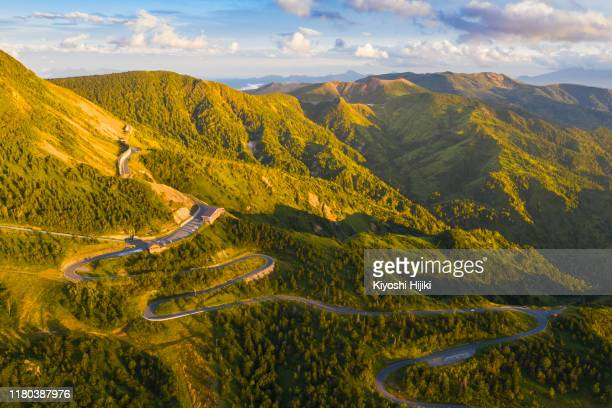 aerial view of winding road on mountain in autumn - 谷 ストックフォトと画像