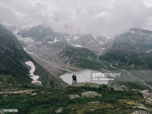 Aerial view of woman and man near the  lake in Swiss alps