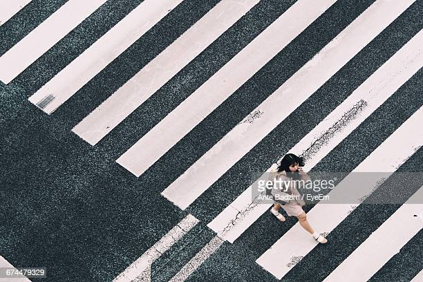 aerial view of woman crossing zebra - pedestrian crossing stock photos and pictures