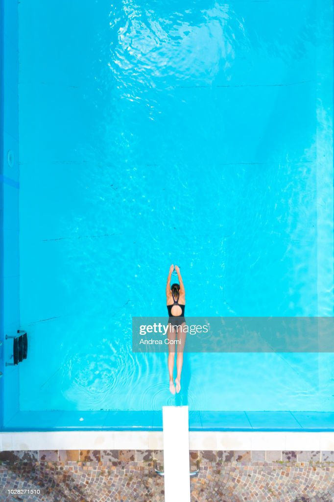 Aerial view of woman diving into swimming pool : Stock Photo