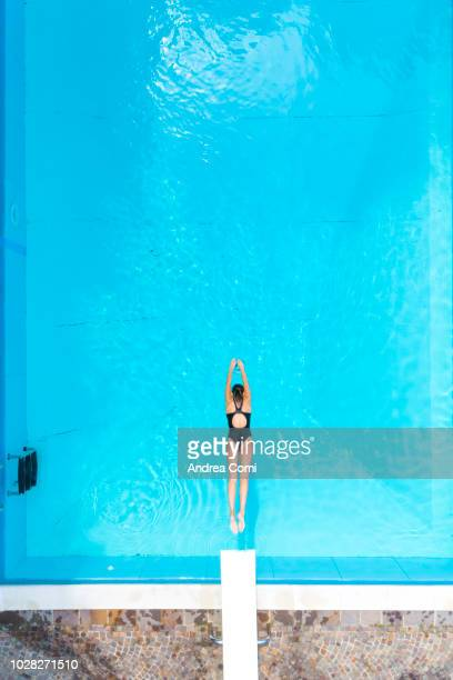 aerial view of woman diving into swimming pool - auf dem wasser treiben stock-fotos und bilder