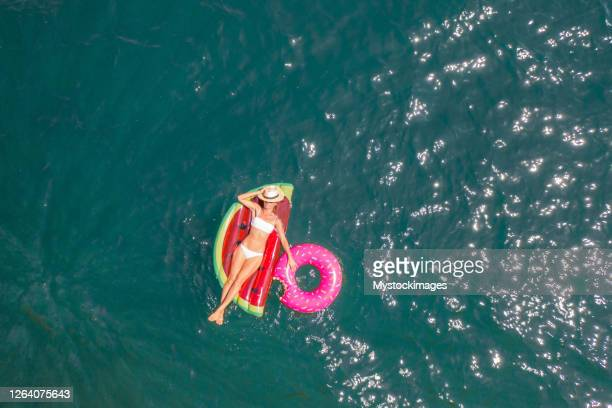 aerial view of woman floating on lake with inflatable mattress sunbathing - inquadratura da un aereo foto e immagini stock