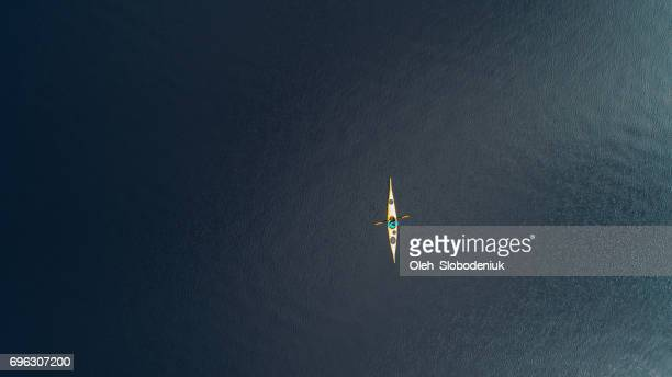 Aerial view of woman kayaking on the lake in mountains