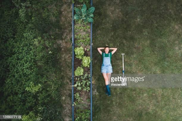 aerial view of woman lying by raised bed on land in yard - hände hinter dem kopf stock-fotos und bilder