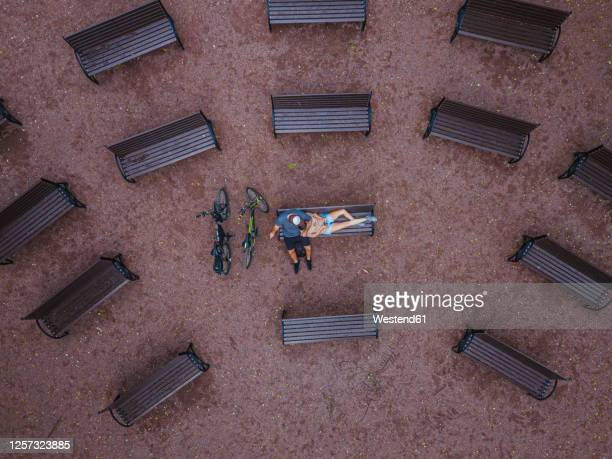 aerial view of woman lying on boyfriend's lap sitting over park bench - park bench stock pictures, royalty-free photos & images