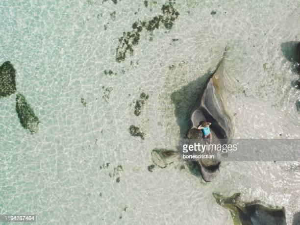 aerial view of woman lying on rock in sea - bortes bildbanksfoton och bilder