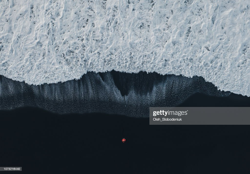 Aerial view of woman on black sand beach in Iceland : Stock Photo