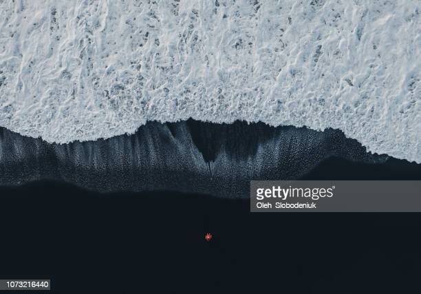 aerial view of woman on black sand beach in iceland - drone stock pictures, royalty-free photos & images
