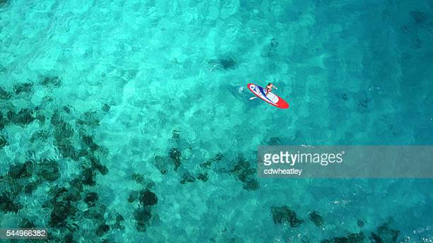 aerial view of woman on paddleboard - watervaartuig stockfoto's en -beelden
