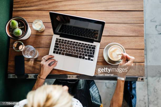 aerial view of woman using laptop and drinking coffee - フリーランス ストックフォトと画像
