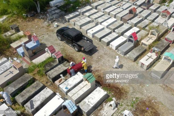 TOPSHOT Aerial view of workers burying a coffin at Maria Canals cemetery in the outskirts of Guayaquil Ecuador on April 12 amid the new coronavirus...