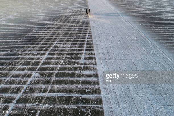 Aerial view of workers using an electric saw to cut the ice into blocks on the frozen Songhua River on December 5 2019 in Harbin Heilongjiang...