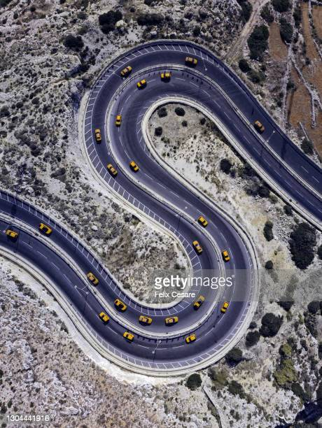 aerial view of yellow cars on a winding road shaped as letter s. - sports track stock pictures, royalty-free photos & images