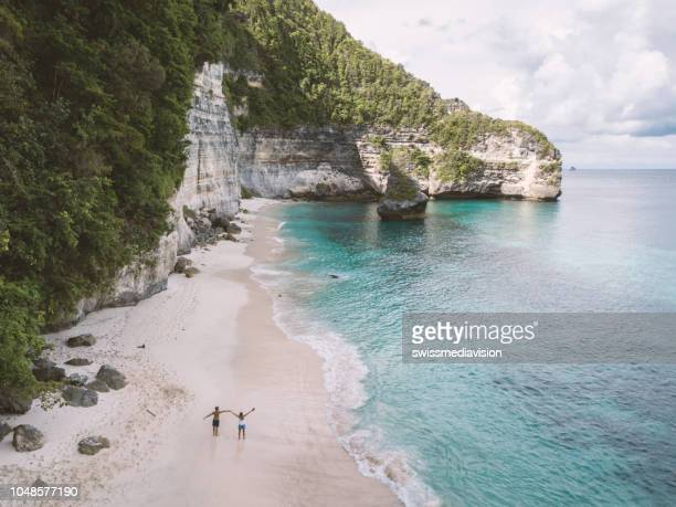 aerial view of young couple on tropical beach enjoying vacations and nature, people travel exploration concept - honeymoon stock pictures, royalty-free photos & images