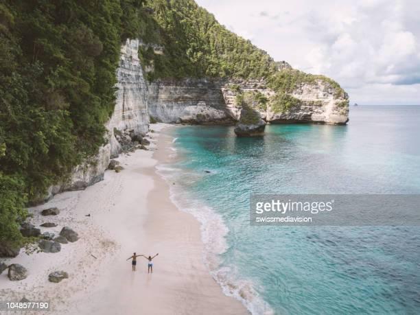luftaufnahme des jungen paares auf tropischen strandurlaub genießen und die natur, reisen menschen exploration konzept - bali stock-fotos und bilder