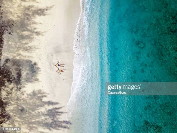 aerial view of young couple relaxing on beach in indonesia - indonesia foto e immagini stock