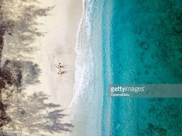 vue aérienne du jeune couple de détente sur la plage en indonésie - s'évader du réel photos et images de collection