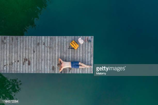 aerial view of young man in bathing shorts laying on jetty at the lake. - jetty stock pictures, royalty-free photos & images