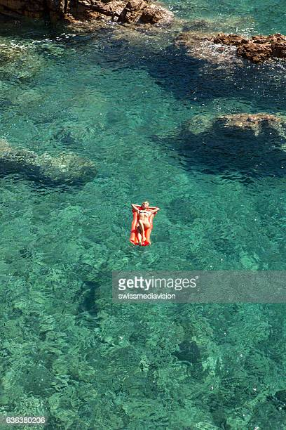 Aerial view of young woman floating on pool mattress