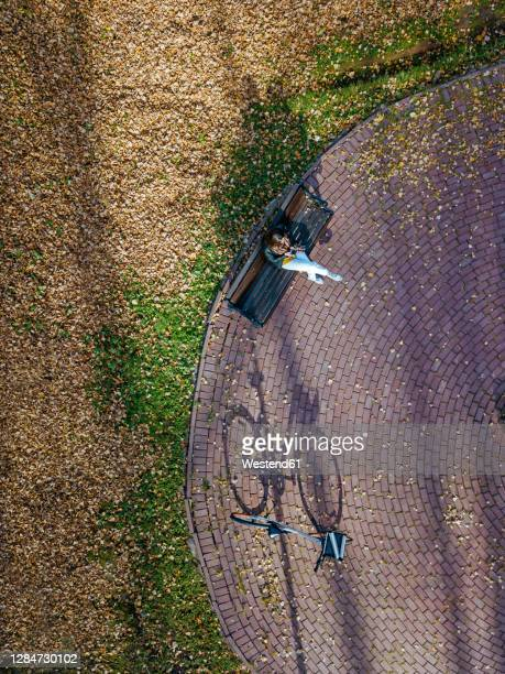 aerial view of young woman sitting alone on bench in autumn park - park bench stock pictures, royalty-free photos & images