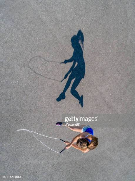 Aerial view of young woman skipping rope, shadow