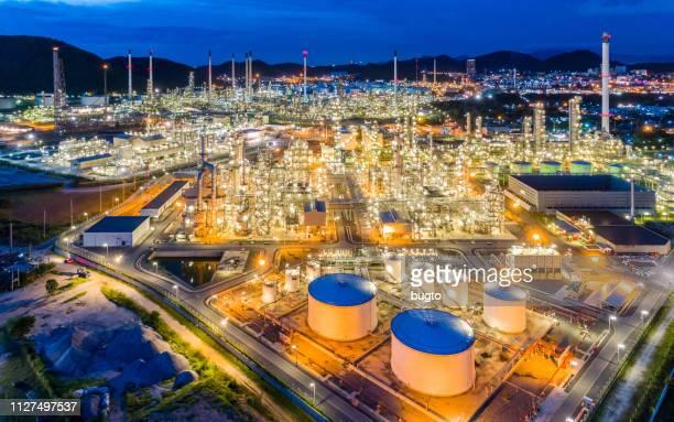 aerial view oil refinery of illuminated factory in the city at night. - planta petroquímica fotografías e imágenes de stock