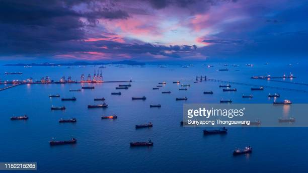 aerial view oil ship tanker park on the sea at dusk with beautiful sky waiting for load/unload oil from refinery for transportation. - motor oil stock pictures, royalty-free photos & images