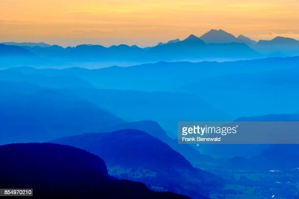 Aerial view on a landscape with mountain ridges and fog in the valleys at sunrise from Vogel cable car hill station at Lake Bohinj Bohinjsko jezero...
