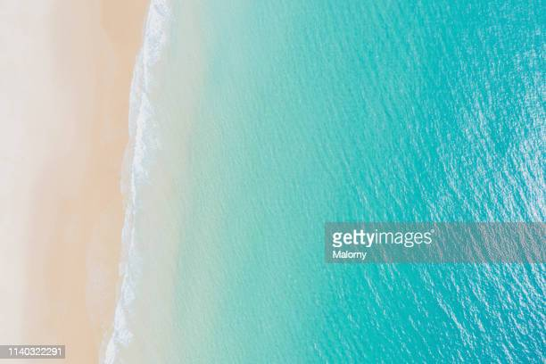 aerial view on empty beach and turquoise sea. directly above. drone view. - turquoise colored stock pictures, royalty-free photos & images