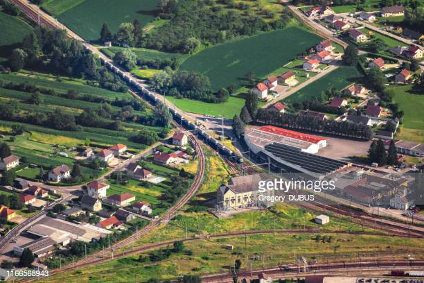 aerial view on freight train arriving on culoz town railroad track junction, with old building structure, in middle of french countryside in summer, ain department, auvergne-rhone-alpes region - ain france stock pictures, royalty-free photos & images