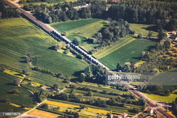 aerial view on freight train railroad track crossing in diagonal the french countryside in summer, in middle of vibrant green fields from ain department, auvergne-rhone-alpes region - ain france stock pictures, royalty-free photos & images