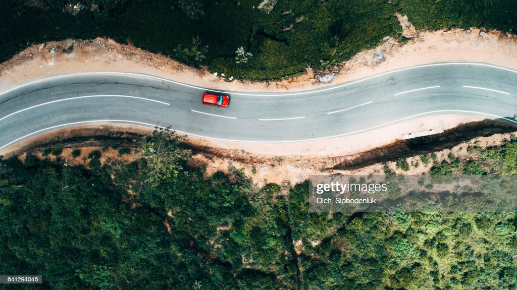 Aerial view on red car on the road near tea plantation : Stock Photo