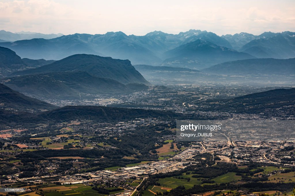 Aerial view on the French city of Chambery and its surroundings at dusk with mist between the Alps mountains : Stock Photo