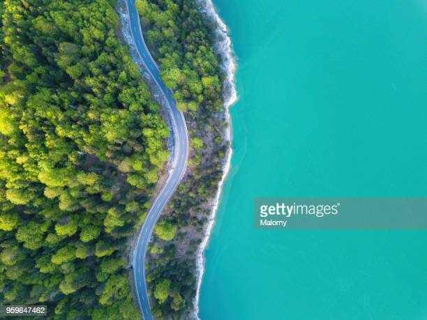 aerial view on turquoise lake sylvenstein and forest with road on the bay. germany, bavaria, lake sylvenstein - küste stock-fotos und bilder