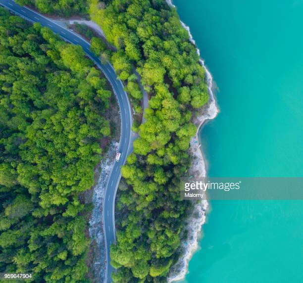 aerial view on turquoise lake sylvenstein and forest with road on the bay. germany, bavaria, lake sylvenstein - landelement stockfoto's en -beelden