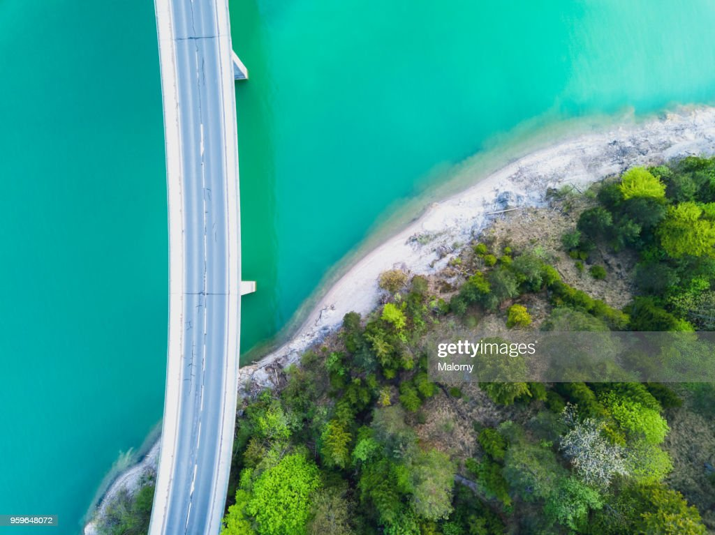 Aerial view on turquoise Lake Sylvenstein and forest with road on the bay leading over the water. Germany, Bavaria, Lake Sylvenstein : Stock-Foto
