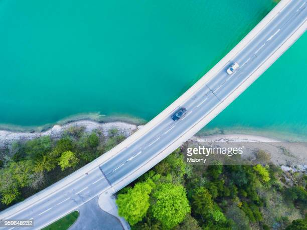 aerial view on turquoise lake sylvenstein and forest with road on the bay leading over the water. germany, bavaria, lake sylvenstein - drohnenperspektive stock-fotos und bilder