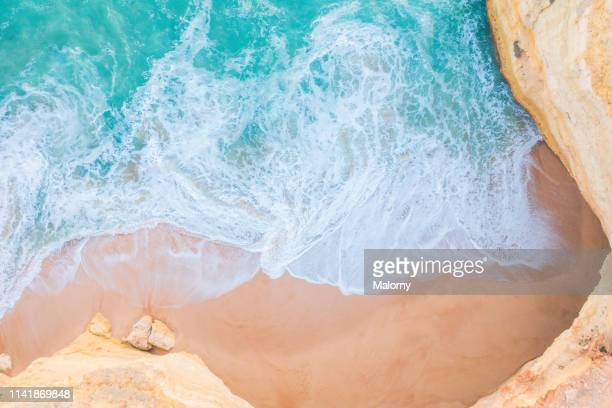 aerial view or drone view: empty beach, turquoise sea and cliffs - sagres stockfoto's en -beelden